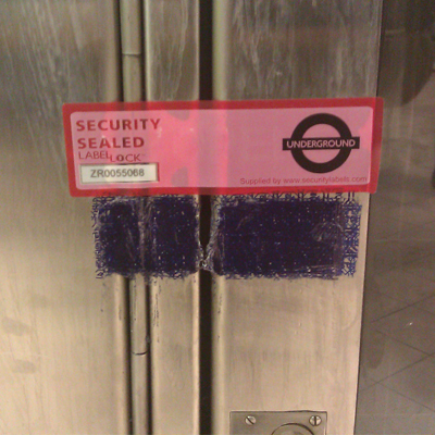 A custom Label Lock ™ low residue security (in red) used to replace a high residue security label solution that was leaving an undesirable, messy residue on the London Underground